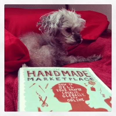 Murchie lays atop a red bedspread, his ears perked. In front of him sits a trade paperback copy of The Handmade Marketplace, featuring a red silhouette of a two-faced girl against a robin's egg blue background.