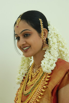 Keralite bride with golden ornaments hanging down from her hair.