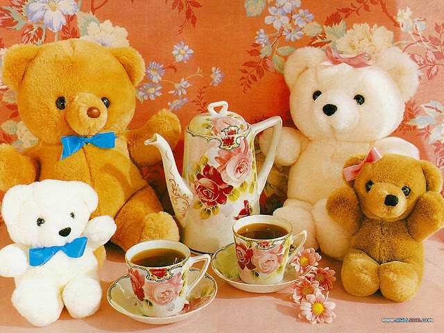 four teddy bears and a rose covered tea pot with two cups against an orange flowered pillow