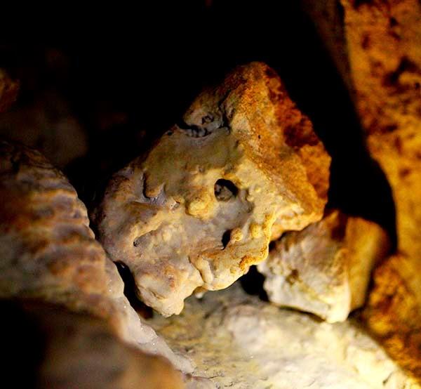 Entramos a un pequeño hueco donde cabemos justos los cinco que formamos el grupo. Ahí Lourdes nos muestra un falo de barro resguardado por otro guardián: una extraña cabeza cuadrada.  Nos cuenta que este falo de barro lo colocaron en la cueva para fecundar de forma simbólica la tierra. A unos cuantos metros de este pene de barro nos muestra una piedra grabada con un circulo que representa la vagina de la mujer. Estos símbolos se usaban para las ceremonias de unión de las parejas.