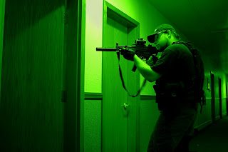 Night vision photo of a SWAT member in an apartment hall.