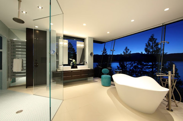 Picture of the bathroom with angled glass wall, white bathtub ans large shower cabin