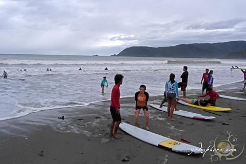 Visitors getting one on one surfing lessons before hitting the waves.
