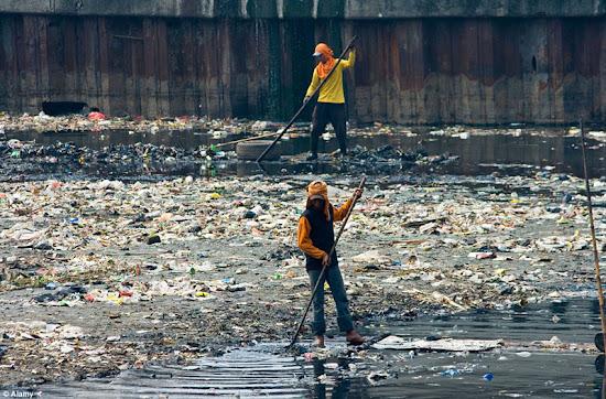 surfista de indonesia deslizándose en ola llena de basura