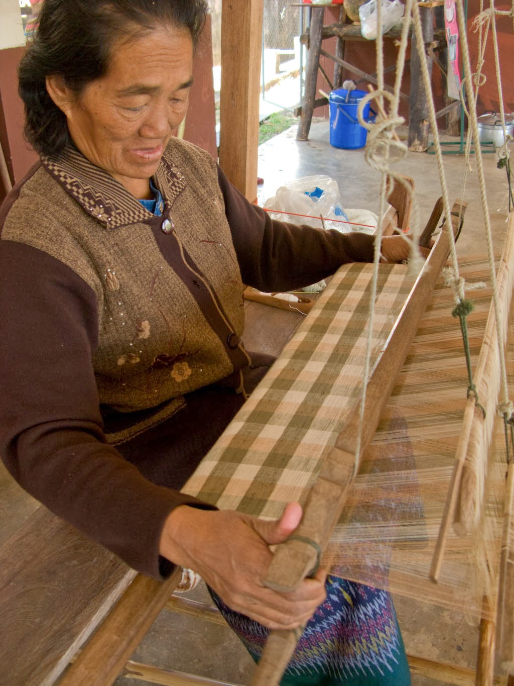 Praphai has been weaving for more than 50 years. Today she weaves a plain cloth in a checked pattern, but her greatest love is to weave every day.