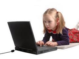 Little girl blogging on computer