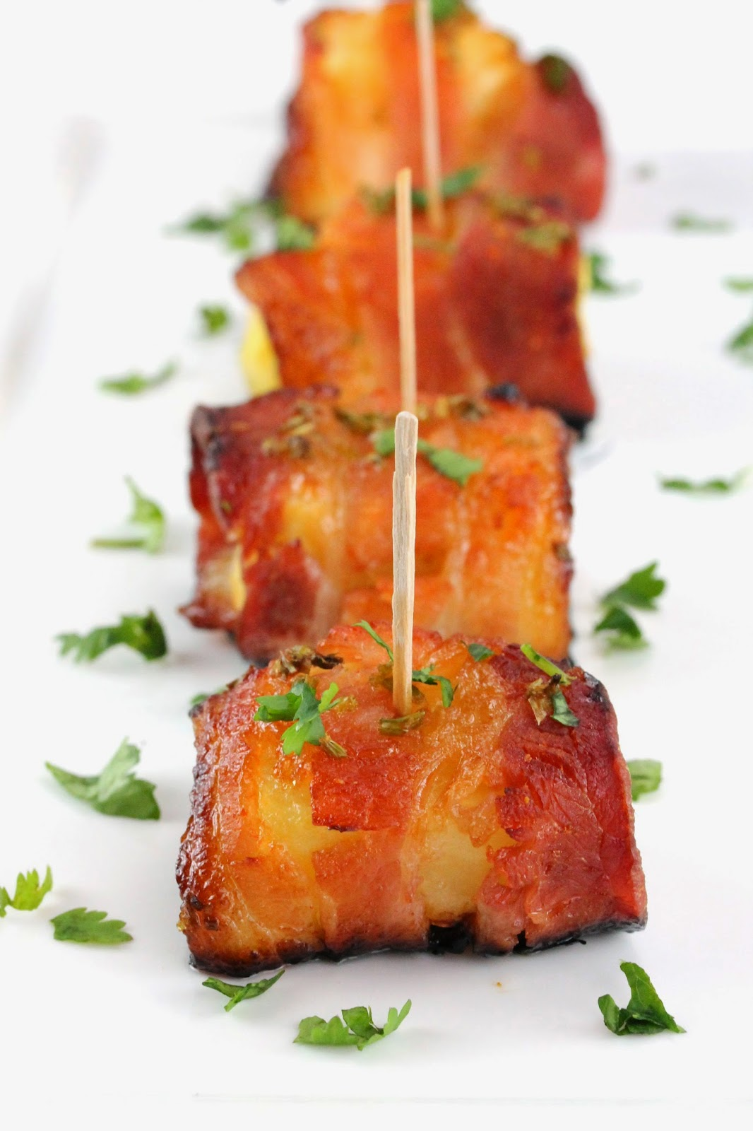 Bacon is wrapped around pineapple and glazed with a sweet and smokey sriracha-honey sauce in this spectacular appetizer.