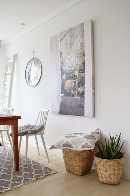 Ansicht der großen Leinwand mit Leitermotiv und vielen Pflanzen sowie Teil des Esszimmertischs mit weißem Stuhl und graugemustertem Teppich