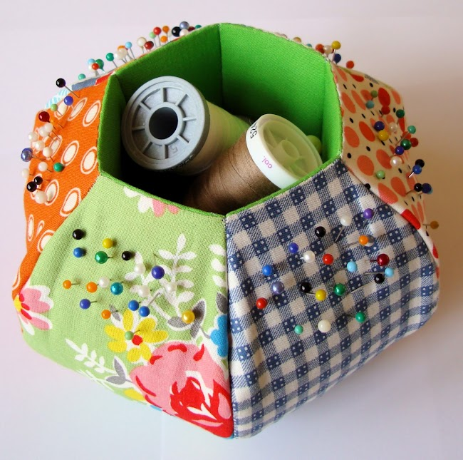 bright fabric pincushion in hexagon shape with a hole in the middle