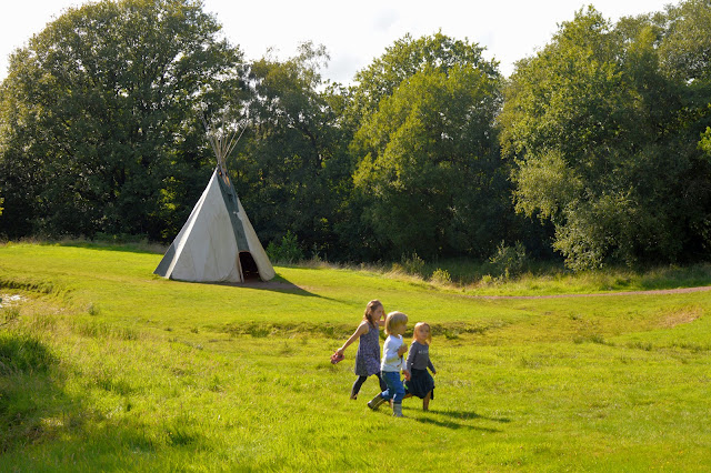 Children walking past an Indian Tipi