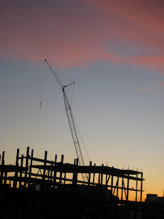 sunset behind the construction of MIT's Koch building