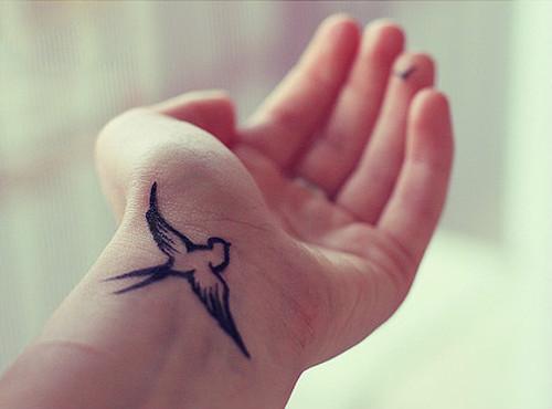 Chica mostrando su tatuaje en la muñeca en forma de pájaro