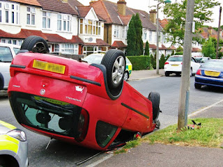 Red car flipped upside down - from rear