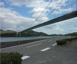 Looking up at the Hakata Oshima bridge from the Shimanami Kaido on Oshima which passes under the suspension bridge section. The Seto sea and Michikajima are visible