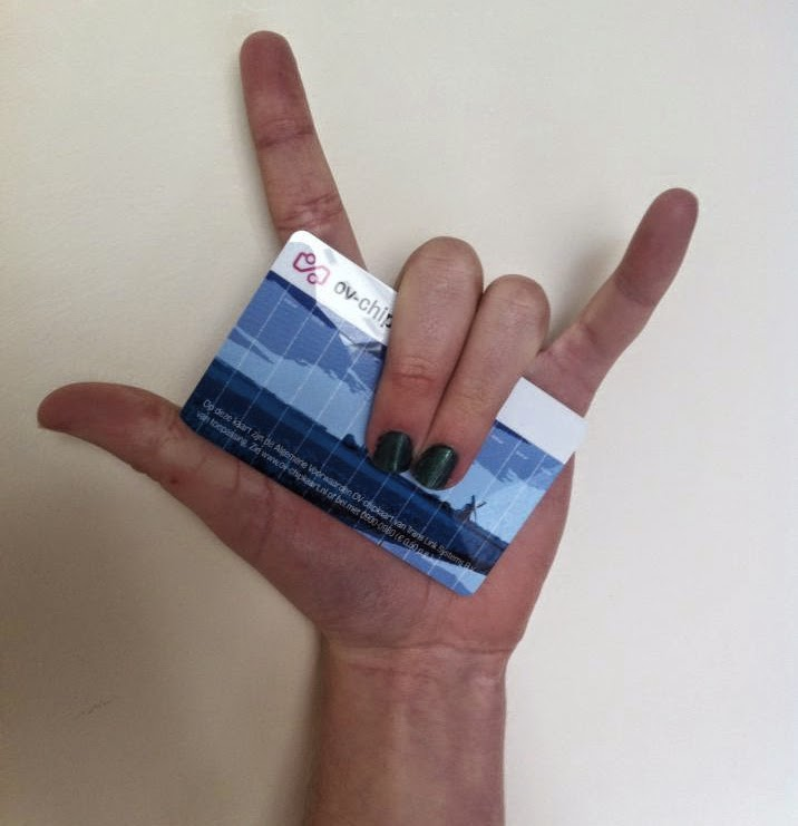 Hand against a white wall. The hand is making the ASL sign for 'love', and holding a dutch train chip card.