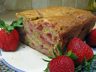 Picture of a loaf of strawberry bread and strawberries on a plate