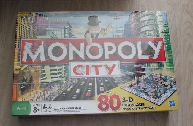 """Monopoly City, med 80 3-D byggnader. """"Tree green houses gives one red hotel"""". Ett klassiskt spel där verkligheten gör sig påmind. Sällskapspel"""