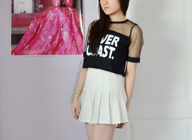 "An edgy, ulzzang-inspired outfit with the ""Never Coast"" black mesh cropped T-shirt from Dresslink and a white American Apparel pleated tennis skirt."