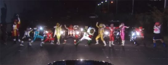 A row of colorful characters appear before a group of headlights, creating a road block.
