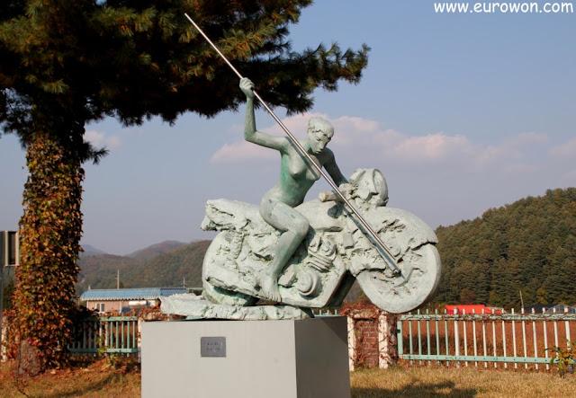 Escultura de mujer sobre moto con lanza
