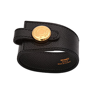 Vintage 1990's black leather Hermes cuff bracelet with gold hardware and snap closure.