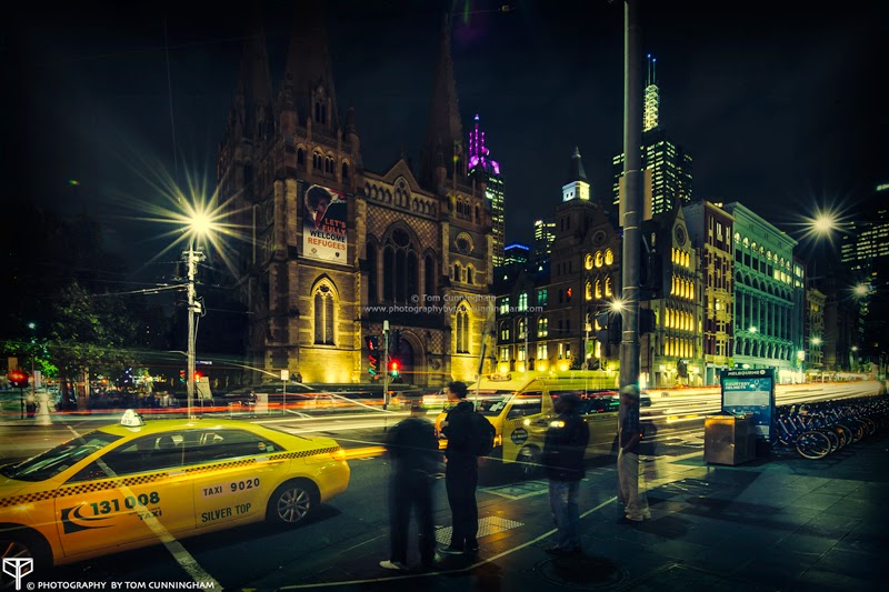 A long exposure photograph by Tom Cunningham of St Pauls Cathedral in Melbourne looking from Federation Square at night with traffic light trails