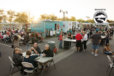 image of food truck feastival with several trucks and guests.