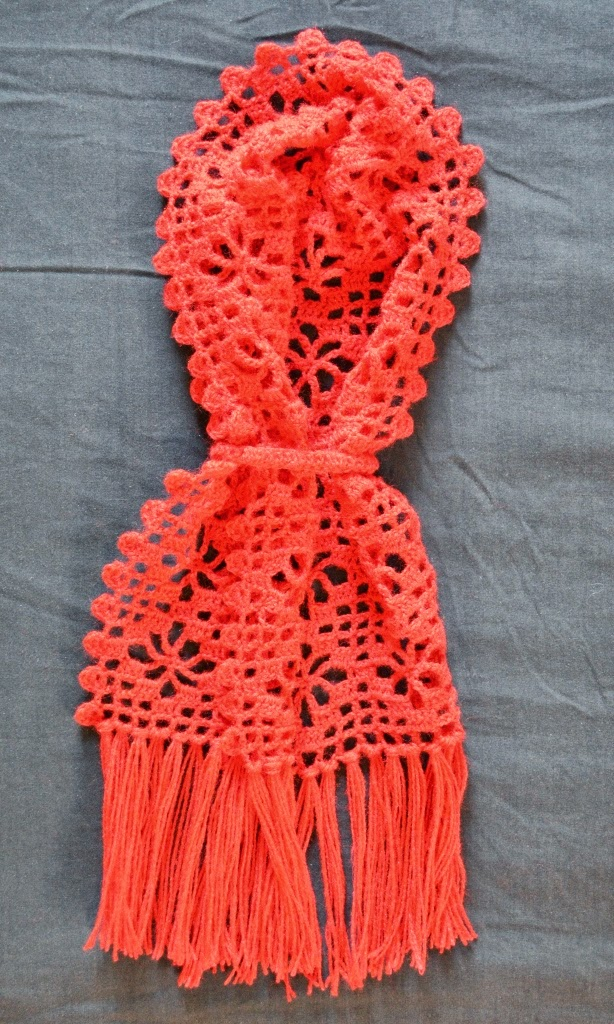 Red filet crocheted Diamond Strike Scarf folded as if to be worn around the neck; two ends are fastened by round band (a crocheted ring) to illustrate the effect of the fringed ends overlapping when worn.