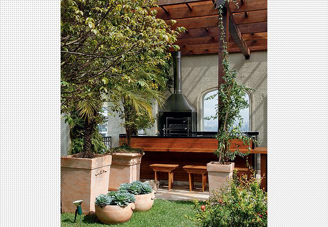 pedras jardim baratas: vegetação do jardim e a bancada em madeira e granito preto absoluto
