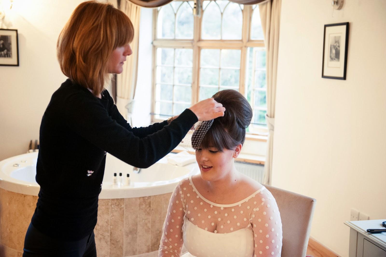 hairdresser fitting vintage style birdcage veil accessory.