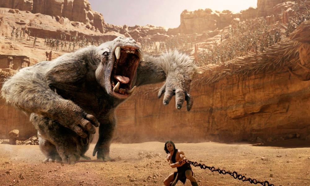 Cena do filme John Carter – Entre Dois Mundos (2012) onde uma criatura gigantesca ataca o herói que está preso a uma corrente