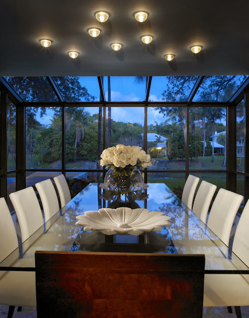 this closer view on the dining room area shows eclectic white furnishings including the dining chairs, white flower center pieces and lighting fixtures with garden view through the customized glass wall and roof
