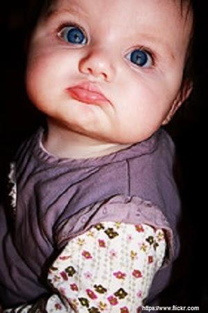 Photo bébé avec yeux bleus qui boude