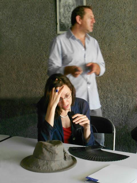 Dolmetscherin im roten Top mit blauer Jacke und Mikrophon einer Personenführungsanlage in der Hand. Vor ihr liegen Hut und Fächer, hinter ihr steht ein jeansbehoster Referent im offenen Hemd.