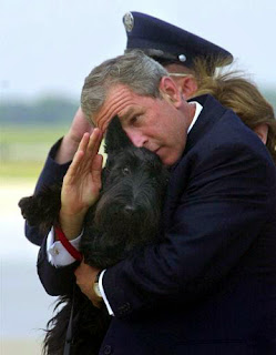 Bush salutes with his dog in his arm