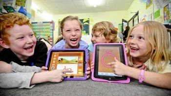Children happily learning using iPads