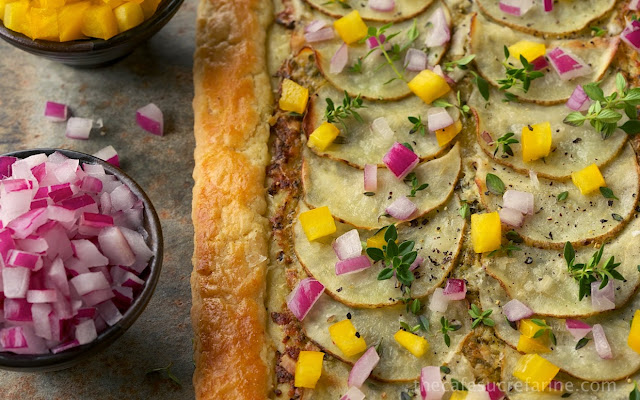 Closeup photo of a Potato Pesto Pepper Galette with bowls of red onions and yellow bell peppers next to the crust.