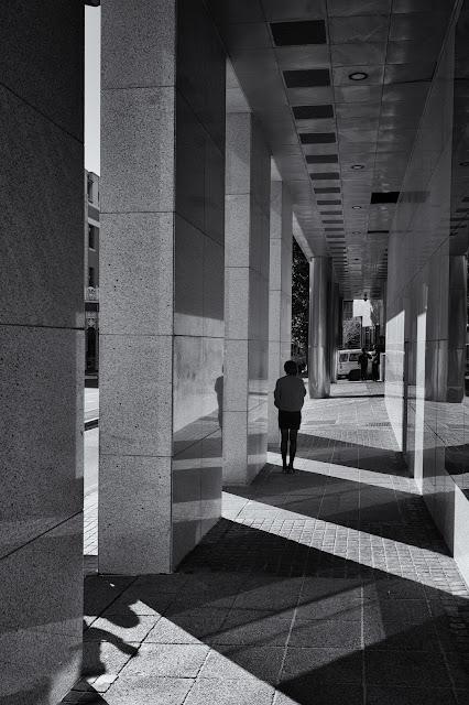 A woman takes  smoke brek behind some columns