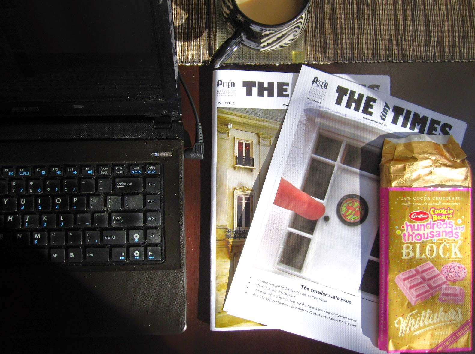 Laptop and mug of tea, with two issues of The tiny Times and a bar of Whittaker's hundreds and thousands chocolate next to it.