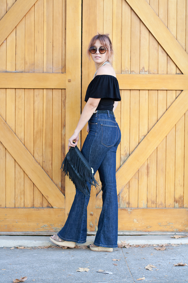 Chic boho style outfits that are easy to wear – bell bottom jeans from current elliot and a black off the shoulder trendy top on Bryn Newman of Stone Fox Style