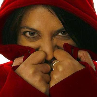 image of woman's face wearing hooded jacket holding upto mouth with both hands