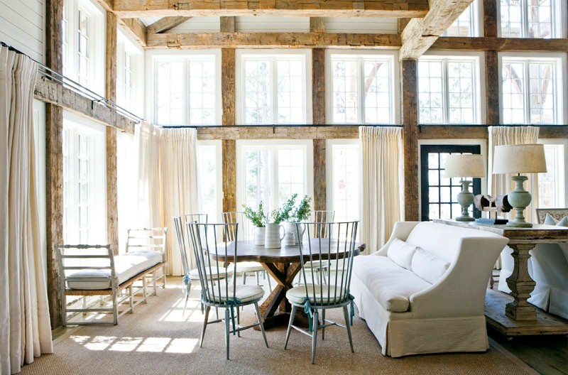 Second seating area in a rustic dining room with high ceiling, exposed reclaimed wood beams, a white sofa, a tree trunk table and light blue metal chairs with white round cushions