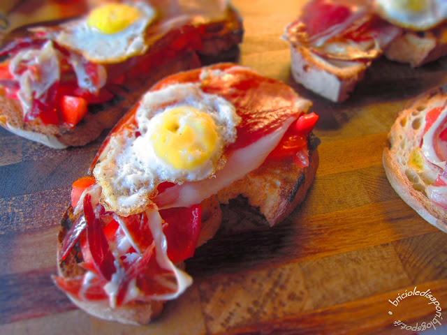 pane casereccio tostato con pata negra, pomodori e uova di quaglia