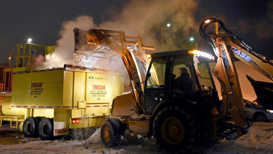 tractor emptying snow into snow melter