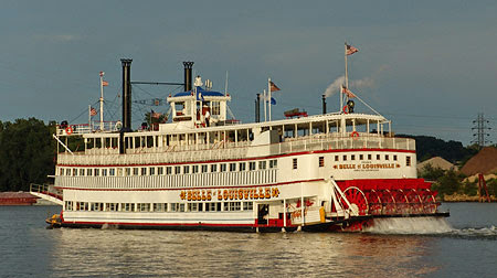 belle of louisville sailing on the ohio river with the smoke stacks in black and the boat with white and red paint