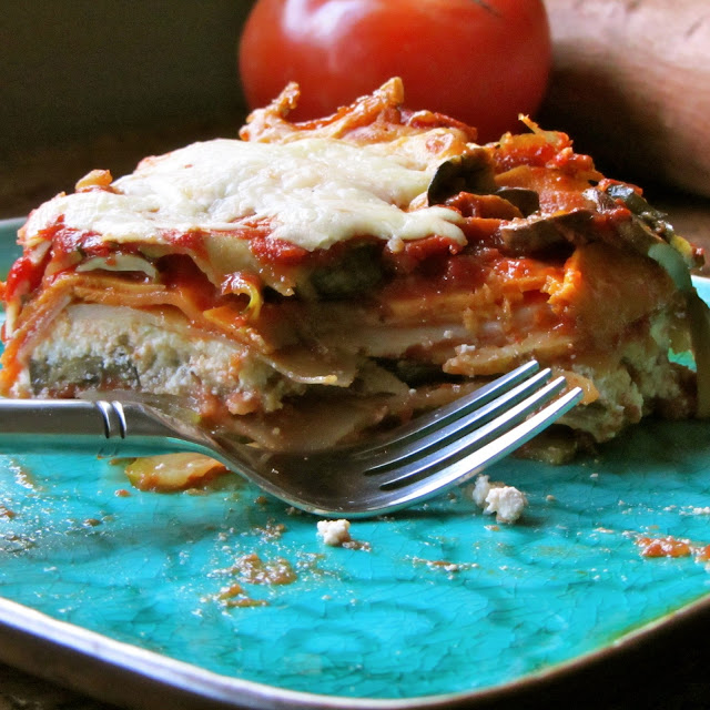 baked veggie lasagna on a blue plate with a fork