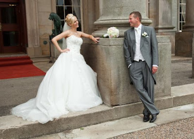 A wedding couple relax outside the front entrance to Wynyard Hall