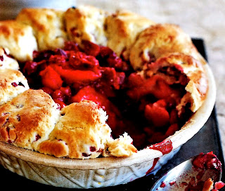 cranberry and apple cobbler dessert with the cobbler topping running around the rim of the cooking dish