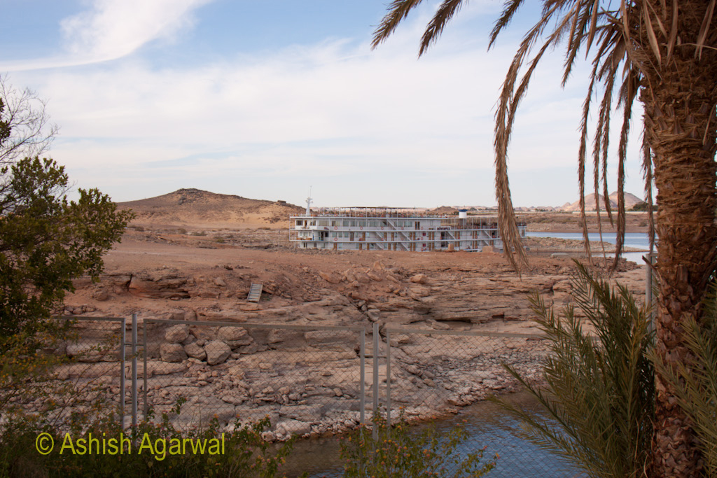 View of tourist ship beyond the security fence of the Abu Simbel temple in Egypt