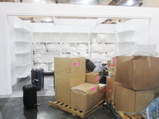 White lacquer display with floating shelves with boxes holding the rest of Nbaynadamas's booth for the New York International Gift Fair